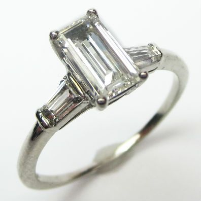 Trim Emerald Cut Ring: For those who like their rings angular, here is a graceful standout with an elegant, elongated emerald cut center stone. Minimalist and sleek, sparkling with bright, well organized bars of light.  Ca. 1960.  Maloys.com