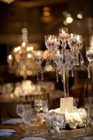 Crystal candelabra nestled in a lush ring of white hydrangea and roses