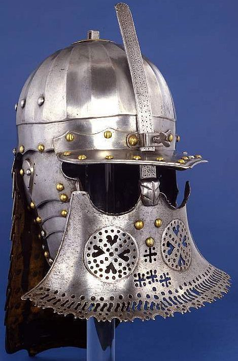 Hussars helmet, Poland, late 17th century, formed of a skull fitted at its front with a separate peak, a sliding nasal-bar fitted at its lower end with a broad face-defence, a long, laminated, medially-ridged neck-defence and laminated cheek-pieces; hammered, shaped, riveted, with fluted, raised, fretted, punched, filed and nicked decoration, with pierced circular ventilations and recessed borders  height: 54.5 cm, width: 30.0 cm, depth: 32.5 cm, weight: 3.87 kg. Fitzwilliam Museum.