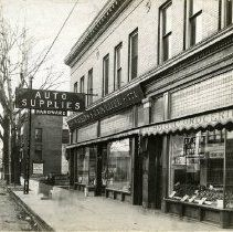 Woodward Avenue between Alexandrine and Willis Streets. Adjacent to Woodward are retail shops including, C.F. Smith Groceries, Watkins and Radcliffe Auto Supplies and Hardware, and J.D. Peterson and Company Furs.c1814