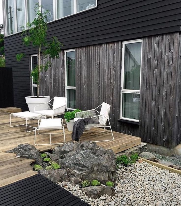 Groovy metal frame white lounge chairs & Ottomans I White plastic pot holder against weathered timber facade