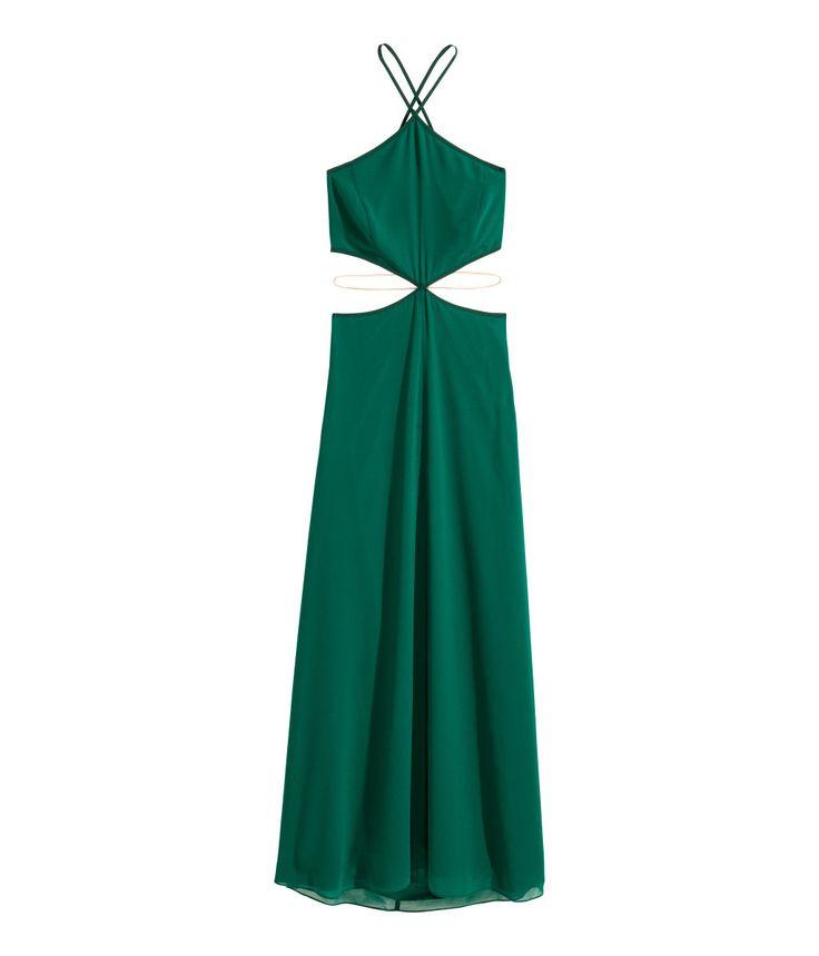 Mørk grønn. En lang chiffonkjole med dekorativ magelenke i metall. Kjolen er todelt og har en bustier og skjørt som sitter sammen midt foran. Åpen i ryggen
