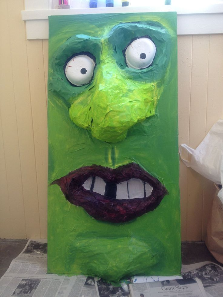 """This face is for a school carnival event. I was asked to make a """"nose picking"""" booth. Kids reach up the nostril for a feel at some goo or a prize (nose-shaped pencil sharpeners!) Very popular, but gross. The face is on a large wood board with hole sawed in middle. I bunched up newspaper and masking tape and shaped the relief image, then gessoed and painted this lovely character."""