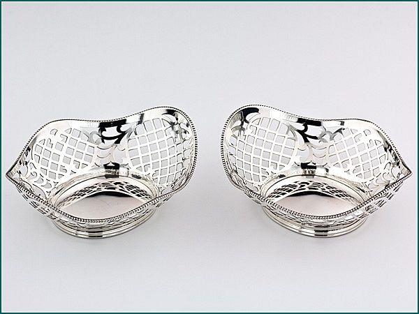 Een stel zilveren bonbonmandjes uit 1962 - Een stel Hollands zilveren bonbonmandjes 2e gehalte Afmeting 12,3 x 10,4 x 4,3 cm Gewicht 125 gram (2) Jaarletter C = 1962 Meesterteken H. Hooijkaas - Schoonhoven