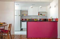 Neste apartamento, a reforma da cozinha trouxe jovialidade e amplitude para a área social. Totalmente branca, a decoração permitiu a ousadia do tom rosa da bancada. Para quebrar o impacto, um tampo de granito preto é colocado, ao lado de azulejos coloridos.