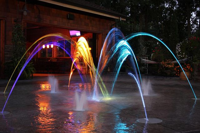 Night time shot of a laminar jet splash pad built using the AquaDirector control box by S.R.Smith.