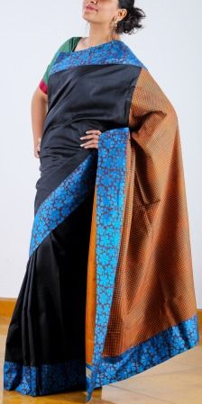 A Bewitching Black Beauty indeed! Black Kanchipuram saree with copper sulphate blue floral block printed border is given a twist with its maroon and green prints that looks like  micro checks on the orange pallu. SHOP AT www.ubikaa.com