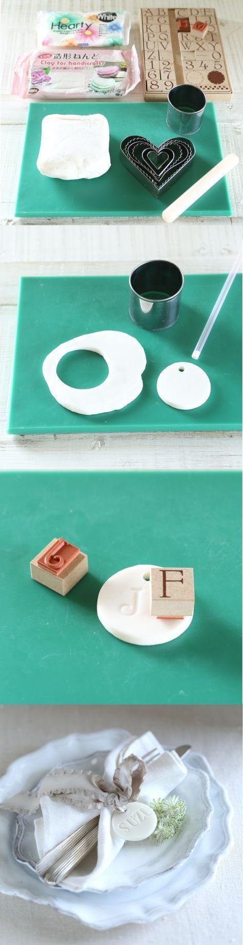 [DIY]粘土で作る陶器みたいなネームプレート 粘土+スタンプで作るネームプレート(席札)。クッキー型で粘土を抜いて、ゲストのイニシャルや名前をスタンプすれば完成する簡単な手順ながら、仕上がりは陶器のような高級感ある印象に。席札以外にも「ENJOY」や「LOVE」など可愛い言葉をスタンプして、ギフトにアクセントとして飾ったり、会場ディスプレーのオーナメントとして使うのも◎