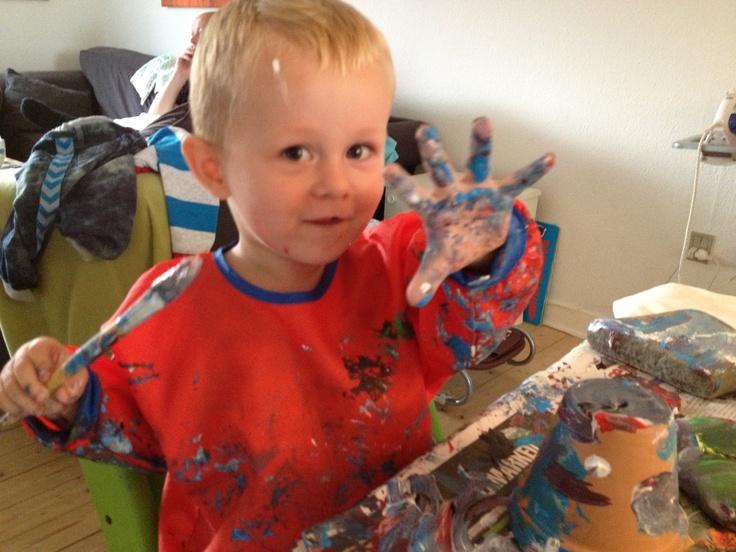 Julegaveproduktionen er så småt gået i gang. Her maler min ældste søn, Liam på 2 år, urtepotteskjulere og sten. På stenene skriver vi navne, når de engang er tørre. Han elsker at male, og kan bruge lang tid på at blande farver og male på forskellige ting.