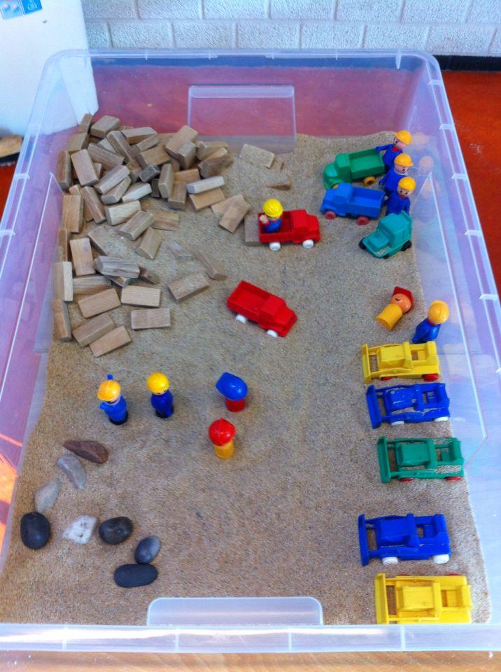 Bouwplaats met schelpenzand, werkvoertuigen en blokjes om mee te bouwen.
