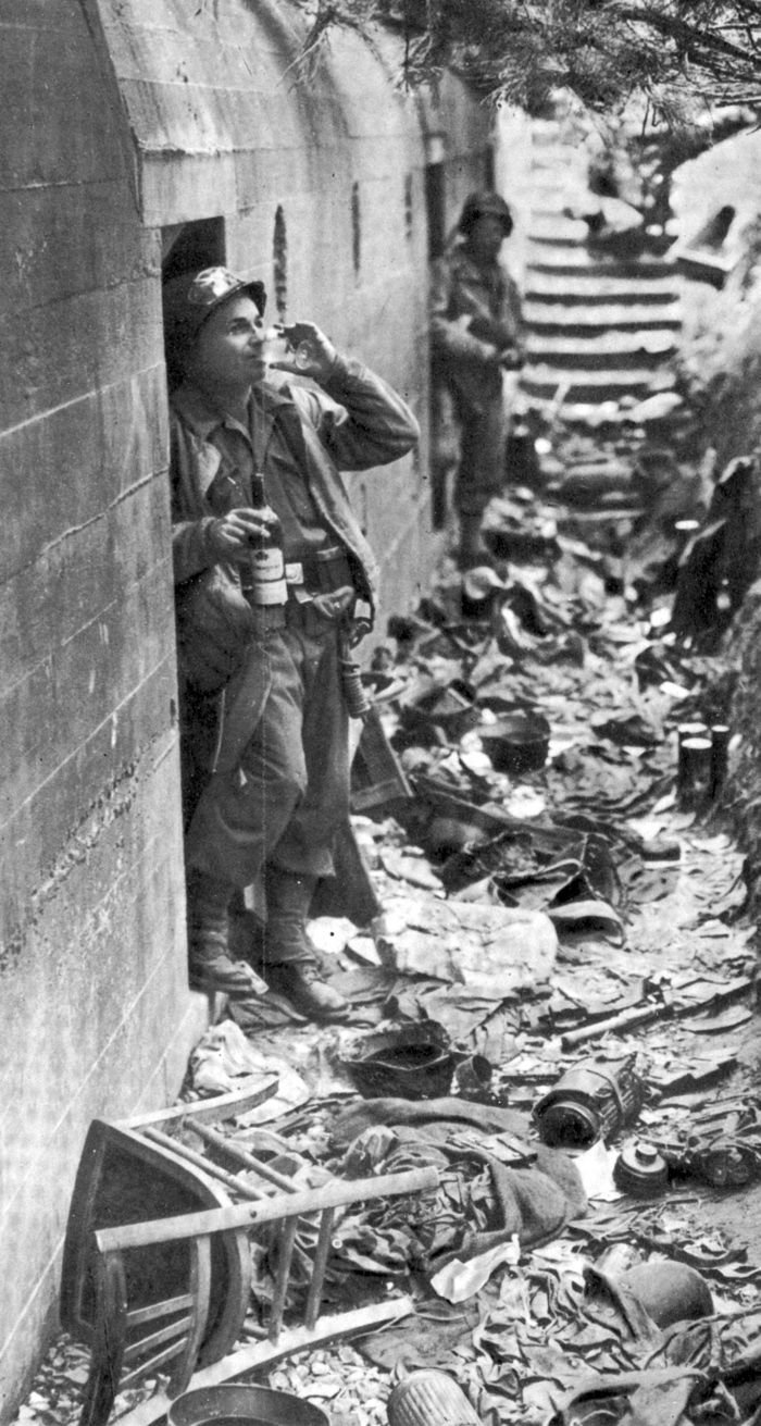 "June 6th 1944, D-Day, American GI drinks ""liberated"" cognac from inside German a bunker."