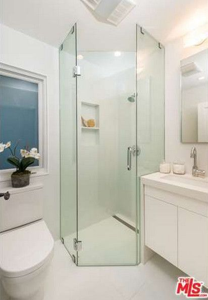 Glass shower walls prevent this petite bathroom from feeling too crowded. The mirror, window, and white palette also opens up the space.