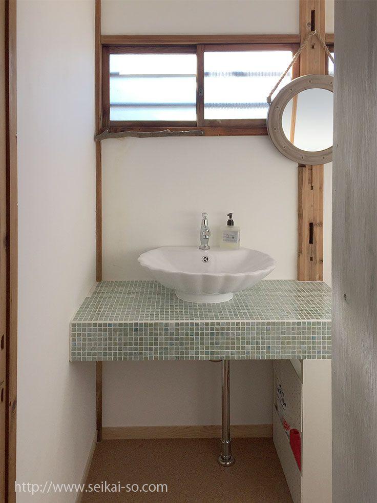 トイレ洗面台 シェル型の洗面ボウルと窓の下に椿の枝のタオル掛け トイレ 洗面台 洗面台 洗面所