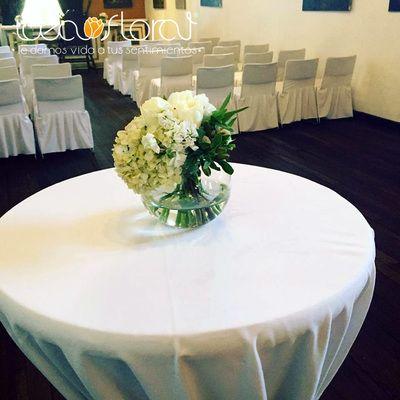Centro de mesa hecho con rosas blancas, hortensias y follaje verde.