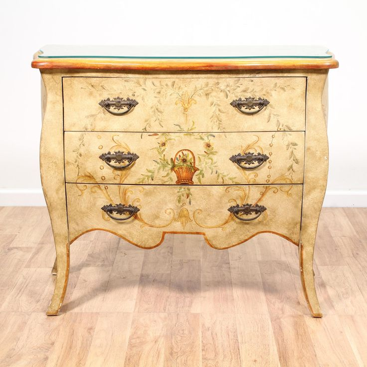 This french provincial chest of drawers is featured in a solid wood with a faux beige antique paint finish. This commode dresser is in great condition with 3 large drawers, a durable glass top and carved curve details. Perfect as an entry console table! #frenchprovincial #dressers #shortdresser #sandiegovintage #vintagefurniture