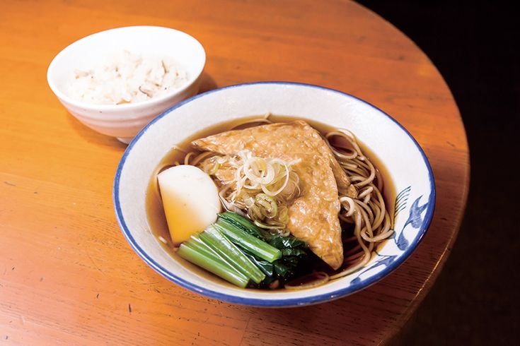 ↑甘過ぎない油揚げに小松菜、かまぼこの 彩りを加えた「きつねそば」。絶品かやくご飯 とのセットは店の人気メニューだ。スタンドそば 満る賀 まるか