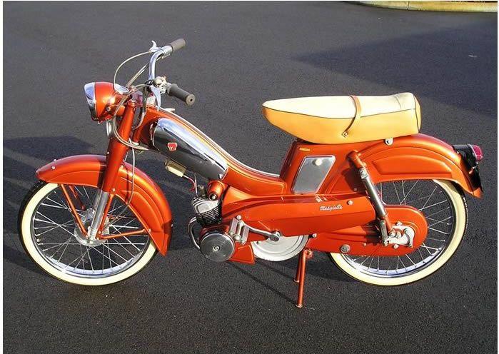 Mobylette orange AV 89 , moteur-monocylindre-deux-temps-49cc-refroidi-par-air-graissage-par-mélange- fourche-télescopique, amortisseurs arrieres, carter de chaine étanche,selle biplace, pneus flancs blanc, Motobécane, Motoconfort-Pantin-France-Europe