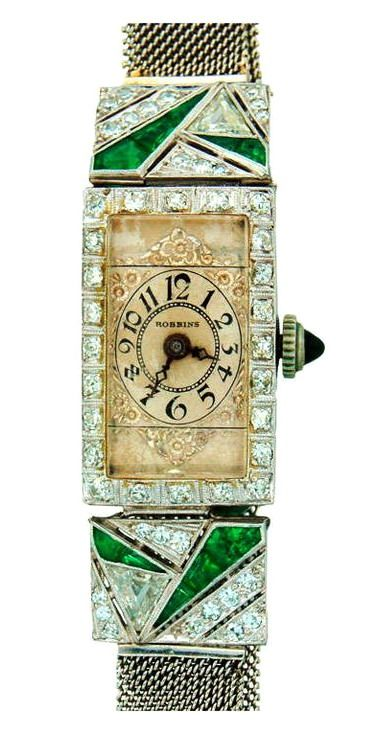 Robbins Lady's Platinum, Diamond and Emerald Art Deco Wristwatch. Elegant Art Deco lady's platinum, diamond and emerald wristwatch, dressy yet wearable. Very tastefully made jeweled timepiece. Fits up to 8-inch wrist. The dial is slightly under 1-inch long, together with the encrusted extensions 1 3/4-inches long, and slightly over 1/2-inch wide. The bracelet is 3/8-inch wide. Manual-wind movement, Swiss made, signed Robbins.