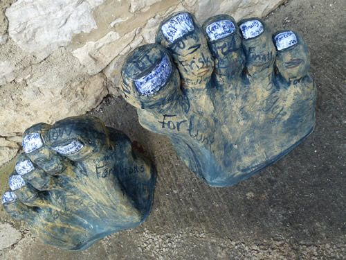"""The Feet of Fate -  Pea Restall Pair of large part feet sculptures with painted words (Hand built slab crank paperclay with internal bridgework structure, oxides s/w fired 1220 and majolica e/w glazed 1110.) Approx. 60cm high x 65cm- 80cm wide x  28cm deep each Only the toes and part of the feet visible- tip of the giant? Toenails are painted with """"F"""" words, excepting the predictable one. Our future is our own and what we make of it."""