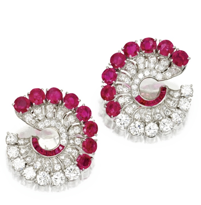 Pair of platinum, ruby and diamond earclips, circa 1935. Of circular design set with round and single-cut diamonds weighing approximately 2.25 carats, accented by round and calibré-cut rubies.