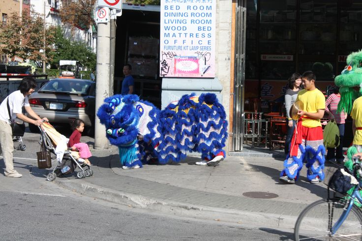 Dragon along Spadina say's hello to a delighted mother and her child