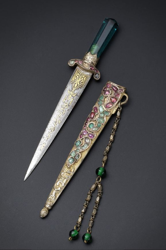 An Ottoman gem-set parcel-gilt miniature Dagger with the tughra of HIH Princess 'Adile Sultan (1825-1898) Turkey, 19th Century the dagger with green glass hilt, the quillons set with rubies and emeralds, the gold damascened blade with an inscription, the gilt scabbard set with further rubies and emeralds and chased to depict a trailing vine, verso with a trailing vine and scale design chape, the suspension loop with a chain with faceted sections and green glass beads