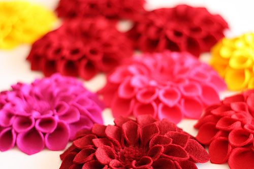 [dahlia corsages in reds, pinks and yellow]