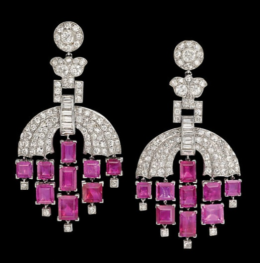 PAIR OF ART DECO RUBY AND DIAMOND EAR PENDANTS, BY CARTIER  Each circular-cut diamond target cluster top, suspending a similarly-set foliate spacer link, to the baguette and circular-cut diamond arching panel and rectangular-cut ruby fringe, circa 1930, 6.1cm long, post fittings, makers case  Signed Cartier, London.  image: Christies