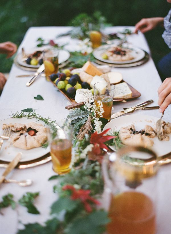Thanksgiving Table - cheese board as centerpiece and lots of natural green with white table cloth