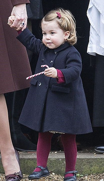 The little Princess Charlotte dressed in festive red tights with a navy coat, and wore her hair tucked behind her ears as she enjoyed a candy cane after church