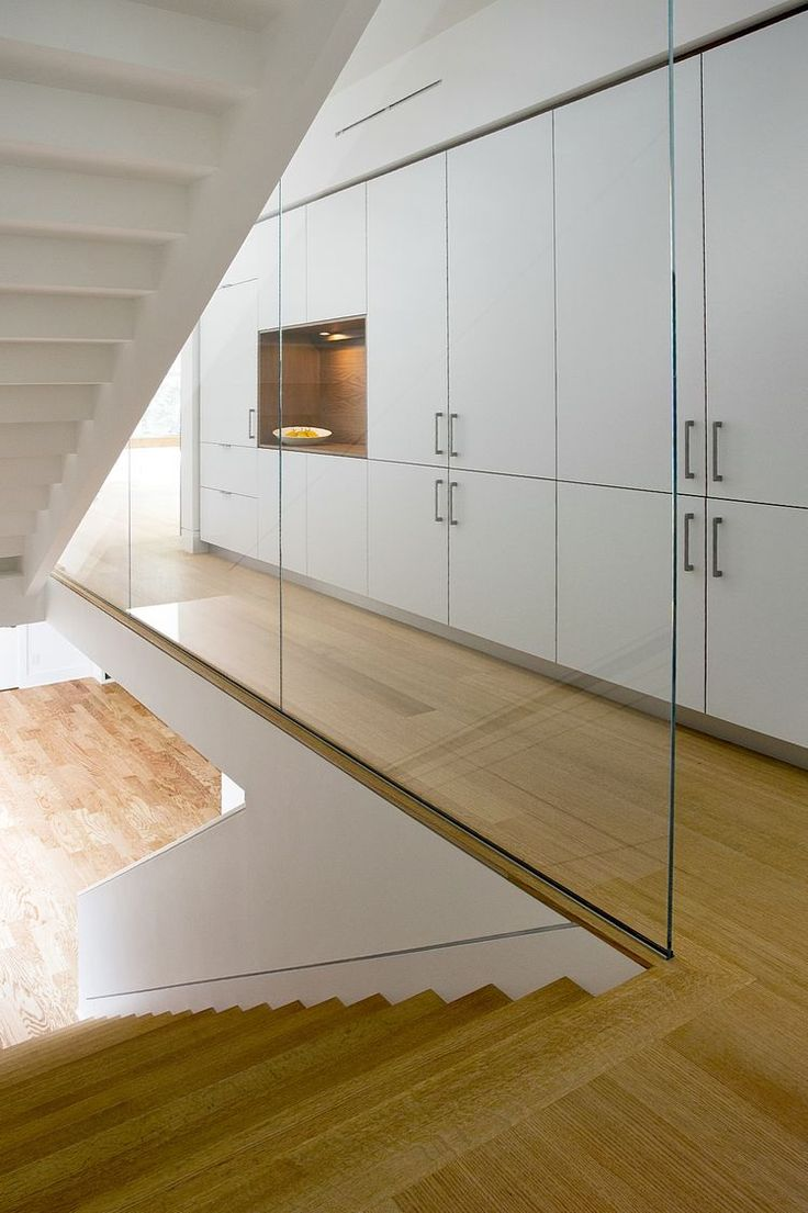 Custom wood and glass staircase next to a wall of cabinets