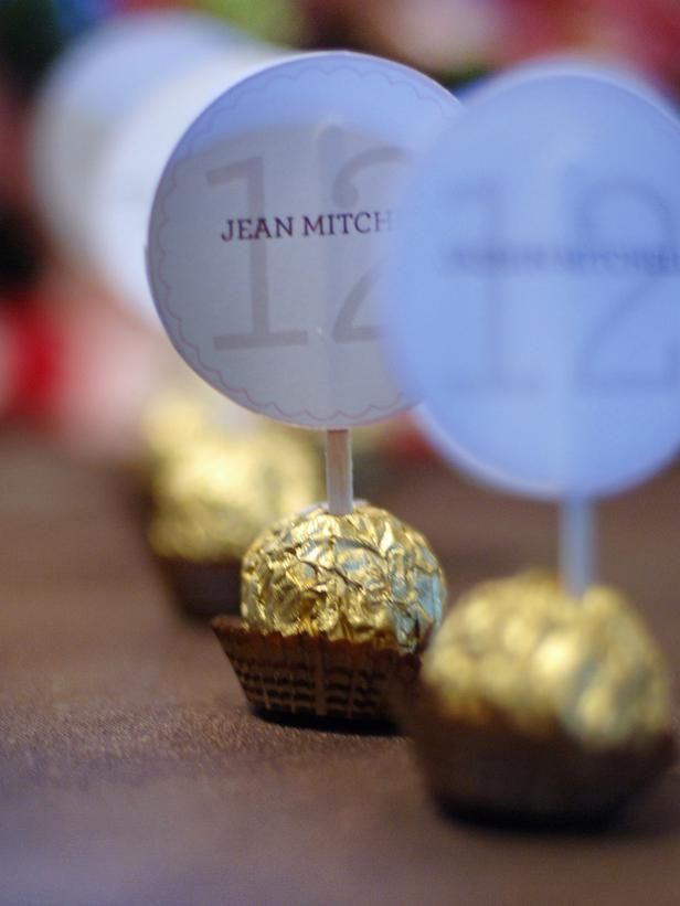 Party favors: Place cards are inserted into Ferrero Rocher candies for a tasty display. To create your own candy seating card, use stirrer sticks and affix labels with the name and table number on them. Then simply push the stick through the center of the candy.