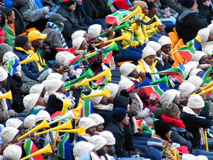 Vuvuzelas - What's plastic, a metre long, brightly coloured and sounds like an elephant? It's the vuvuzela, the noise-making trumpet of South African football fans, and it's come to symbolise the sport in the country. It's an instrument, but not always a musical one. Describing the atmosphere in a stadium packed with thousands of fans blowing their vuvuzelas is difficult. Up close it's an elephant, sure, but en masse the sound is more like a massive swarm of very angry bees.