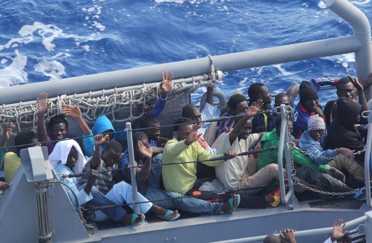 """Distressed persons wave after being transferred to a Maltese patrol vessel.  Coördinator Dodenherdenking in Loenen: """"De vluchtelingen van nu, zijn de verzetstrijders van toen!"""""""