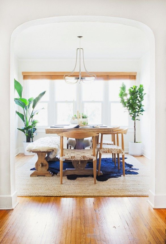 This bright airy dining room is made complete with wooden dining table and chairs, bench seating overlaid with a fur throw, textured area rug and a modern metal chandelier.