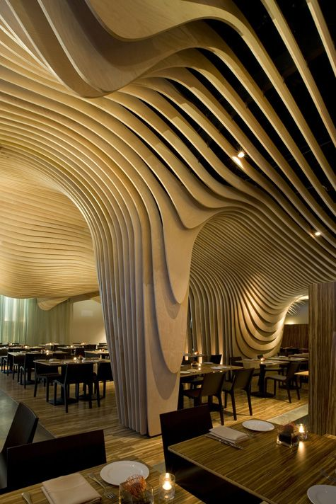 """""""Banq"""" by Office dA received inspiration from a Banyan tree that swirls and flows in a rather organic pattern. The woodsy interior design features layered Birch and recycled bamboo tables.The site was originally the formerly Boston's Penny Savings Bank which is now a hot spot for a multi-cultural dining experience led by chef Ranveer Brar."""