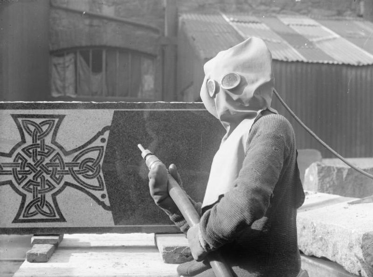WOMEN IN INDUSTRY DURING THE FIRST WORLD WAR, SCOTLAND, c 1918. A female granite worker prepares to sand blast a design on a gravestone at Messrs Stewart and Co., Aberdeen. She is wearing a large protective hood over her head, which has two round 'windows' through which she can see, and a pair of large protective mittens.