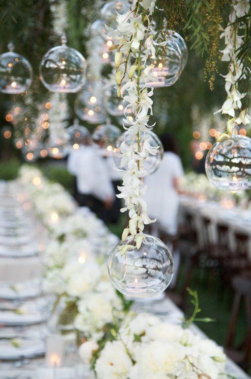 Tea lights inside floating glass bubbles floating over the tables. Estas burbujas de vidrio con una vela de té en cada una, irradia romance sobre la mesa de este jardín para bodas.