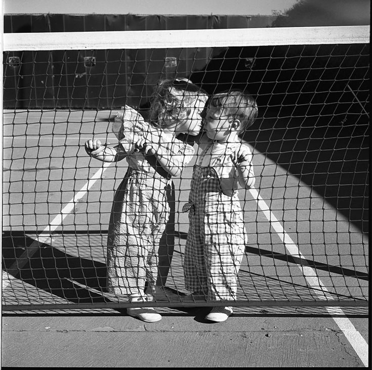 by Vivian Maier : Two Children Kissing at Tennis Net, Los Angeles, August 1955