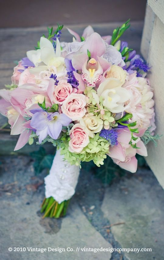 Pretty hydrangea, spray rose, orchid, and freesia bouquet in soft pink, light green, and lavender.