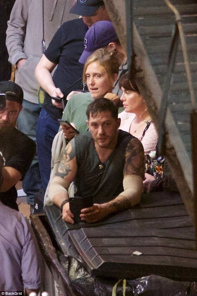 You're dumped: Tom Hardy shows off his bulging muscles in a grey vest as he leans on a dum...