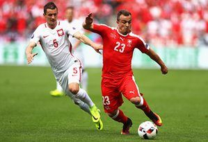 Xherdan Shaqiri of Switzerland skips past Krzysztof Maczynski.