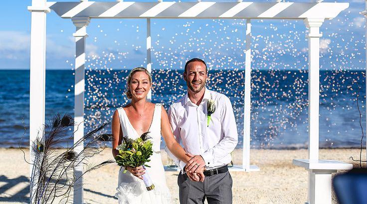 Intimate destination beach wedding under white altar with sparks   Palace Resorts Weddings ®