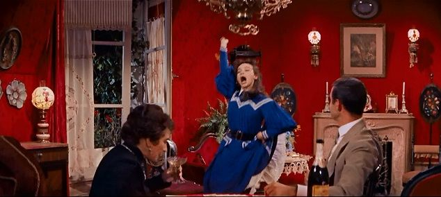 Gigi (1958) - When she's not rushing to and from school and is just lounging around the house, Gigi (Leslie Caron) wears a royal blue dress. Knife pleats, Peter Pan collar, mutton chop sleeves, bright white lines running everywhere contrasting the blue... she's almost clown-like, emphasizing her juvenile qualities at this point in the movie. Hermione Gingold and Louis Jourdan look on.