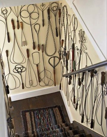 A collection of vintage rug beaters displayed on a staircase wall. Who knew there were so many designs?