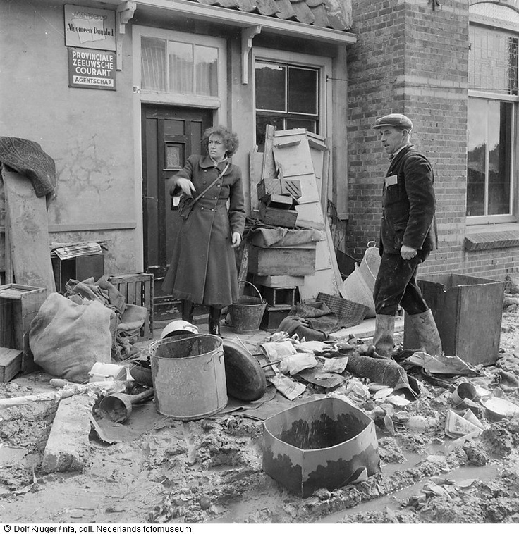 Twee mensen bij de ravage van hun huis.