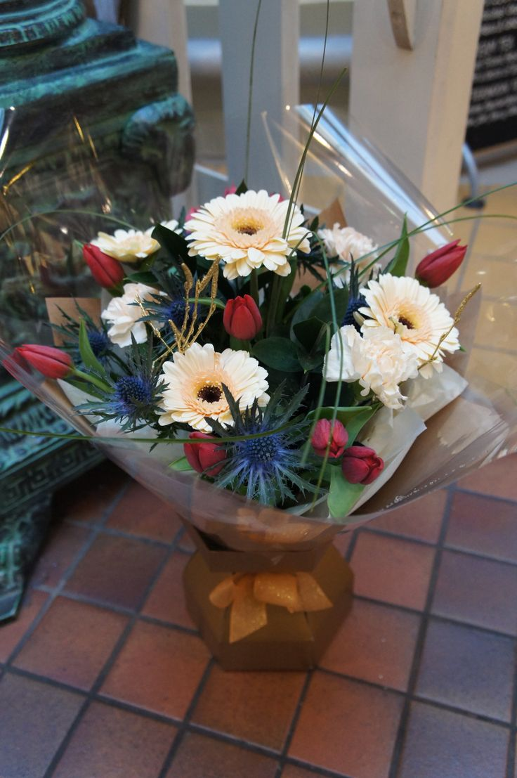 Cream Gerbera daisies, ruby red tulips and bright blue thistle