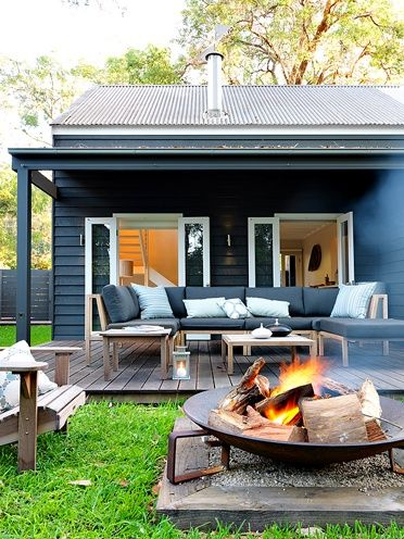 Indoor outdoor space with wooden deck adirondak chairs and firepit, black siding and white trim