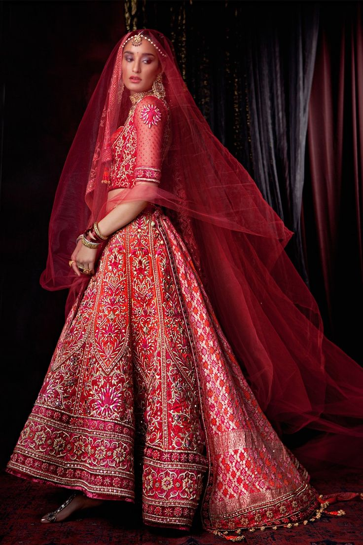 A zardozi embroidered graded bridal lehenga and red wedding veil by Tarun Tahiliani