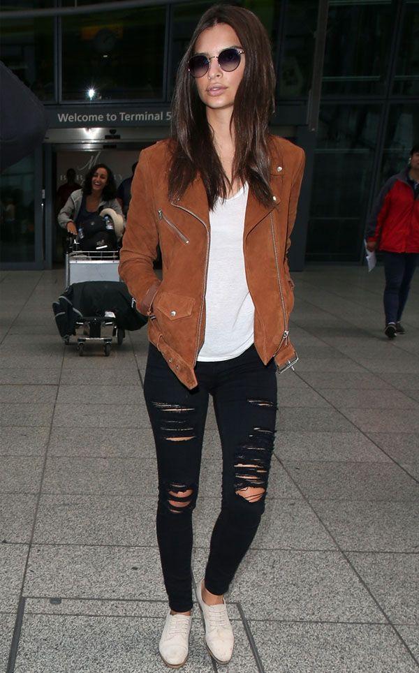 Look de Emily Ratajkowski no aeroporto, com t-shirt branca, calça preta e jaqueta biker marrom.